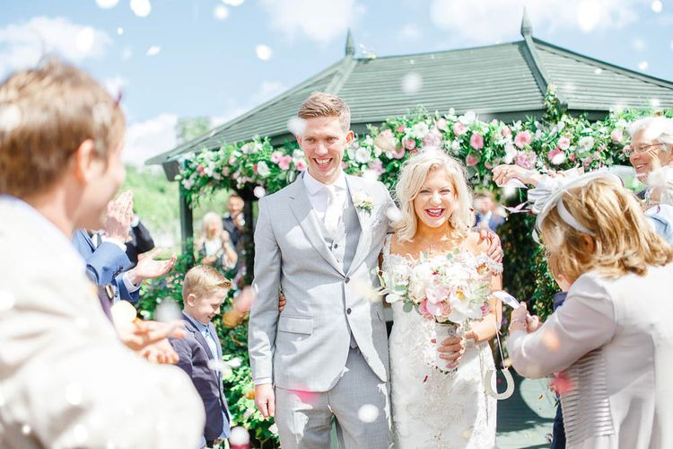 Confetti Exit | Bride in Sottero & Midgley Gown | Groom in Grey Reiss Suit | The Secret Garden Wedding Venue in Essex | White Stag Wedding Photography