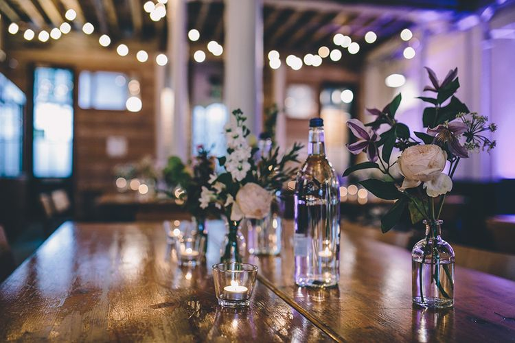 Festoon Lights   Flower Stems in Bottles   Wedding Decor   Stylish London Wedding Planned by Revelry Events   Story + Colour Photography