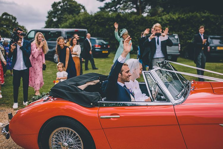 Red Convertible Wedding Car | Bride in Polka Dot Tulle Eponine London Gown | Groom in Charlie Casey Hayford Suit | Classic Marquee Wedding at Kimberley Hall in Norfolk | Story + Colour Photography | Driftend Films