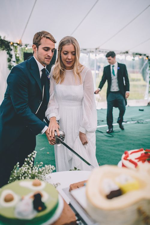 Cutting the Cake | Bride in Polka Dot Tulle Eponine London Gown | Groom in Charlie Casey Hayford Suit | Classic Marquee Wedding at Kimberley Hall in Norfolk | Story + Colour Photography | Driftend Films