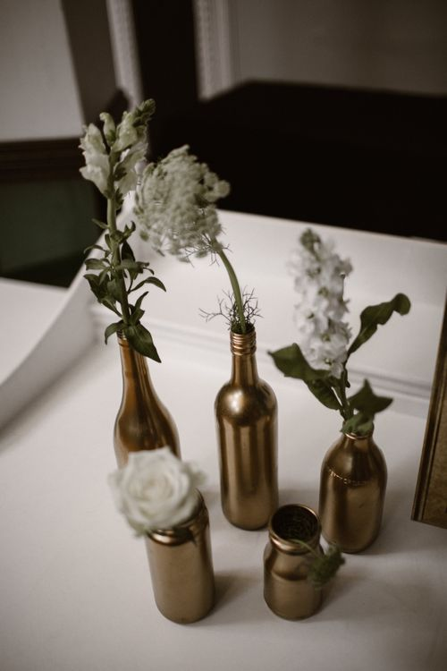 Gold Spray Painted Bottles filled with White Flower Stems