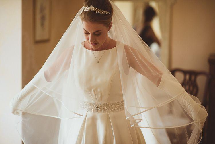 Bride in Tom Flowers Dress, Long Satin Gloves & Ivory & Co. Headdress Getting Ready