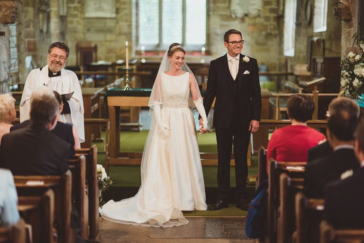 Bride in Tom Flowers Dress, Long Satin Gloves & Ivory & Co. Headdress and Groom in Moss Bros Suit at Church Wedding Ceremony