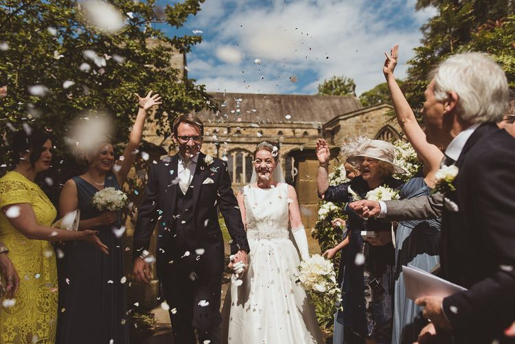 Bride in Tom Flowers Dress, Long Satin Gloves & Ivory & Co. Headdress and Groom in Moss Bros Suit at Church Confetti Exit