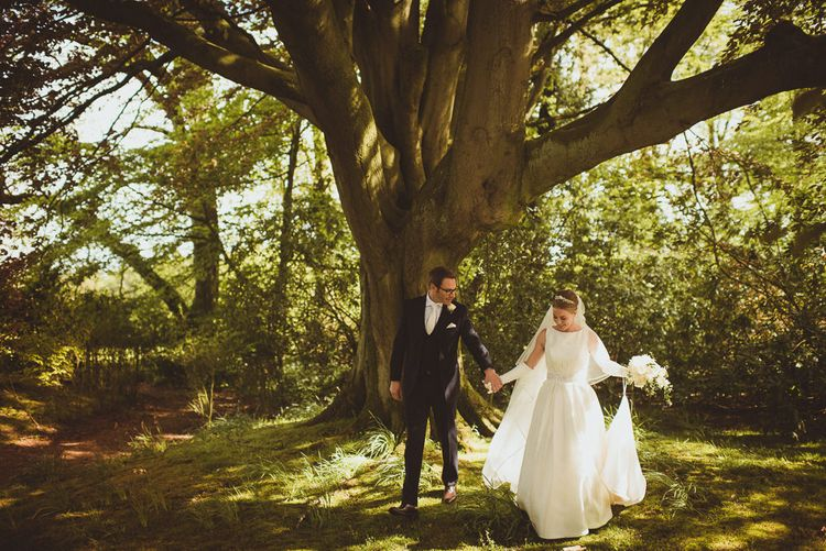 Bride in Tom Flowers Dress, Long Satin Gloves & Ivory & Co. Headdress and Groom in Moss Bros Suit