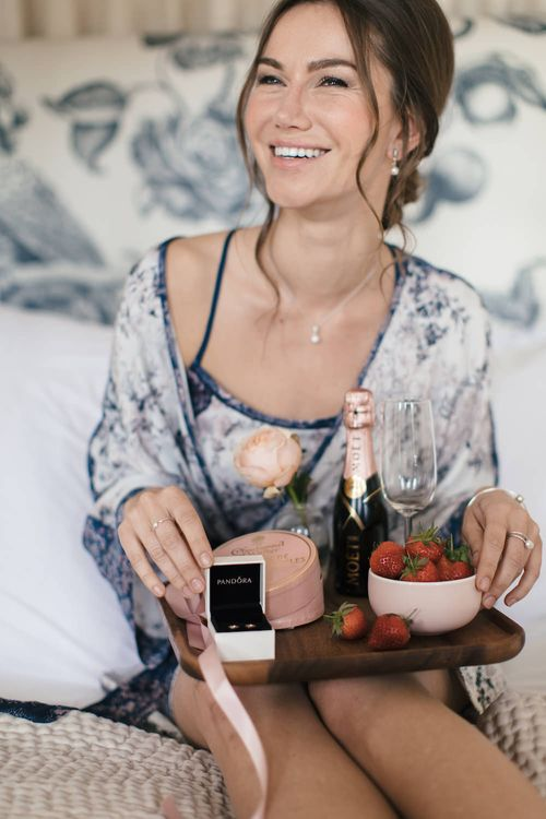 Bridesmaid in floral chemise and breakfast tray with PANDORA rose gold earrings