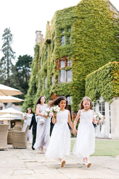 Flower Girls in White Dresses | Outdoor Blush Flower Filled Wedding at Pennyhill Park, Surrey Planned by Something Blue Weddings | Anushe Low Photography | Reel Weddings Film