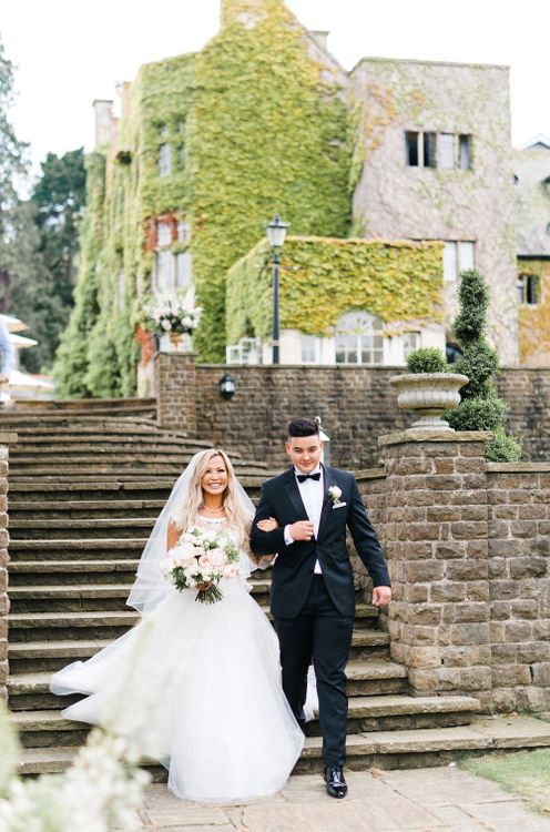 Bridal Entrence in Sassi Holdford Gown | Outdoor Blush Flower Filled Wedding at Pennyhill Park, Surrey Planned by Something Blue Weddings | Anushe Low Photography | Reel Weddings Film