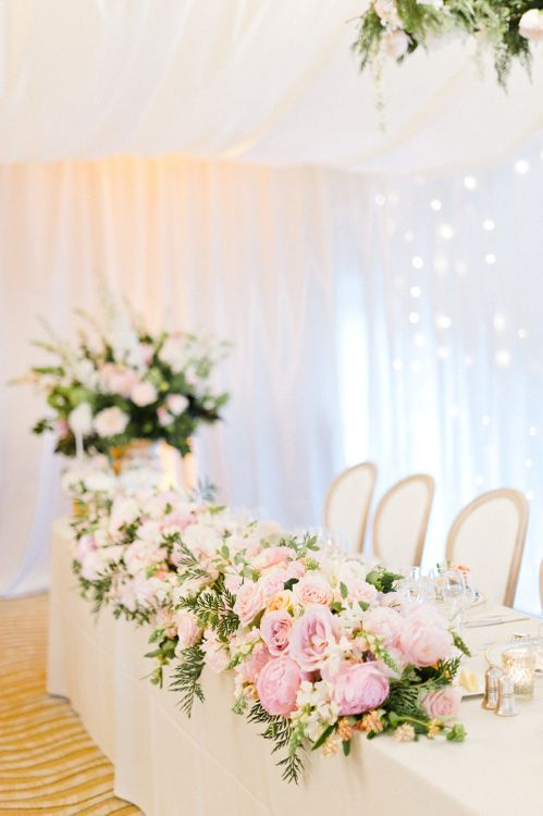 Top Table Floral Display by Blue Sky Flowers | Blush Flower Filled Wedding Reception at Pennyhill Park, Surrey Planned by Something Blue Weddings | Anushe Low Photography | Reel Weddings Film