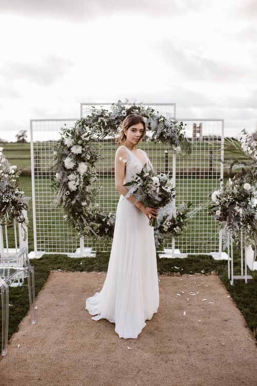 Bride in Watters Wtoo Bridal Gown | Aisle & Altar Style | Moon Gate Floral Arch by Swaffham Florist | Ghost Chairs | Nocturn Wedding Inspiration Planned & Styled by The Little Lending Company | Agnes Black Photography | Film by The Wilde Bride