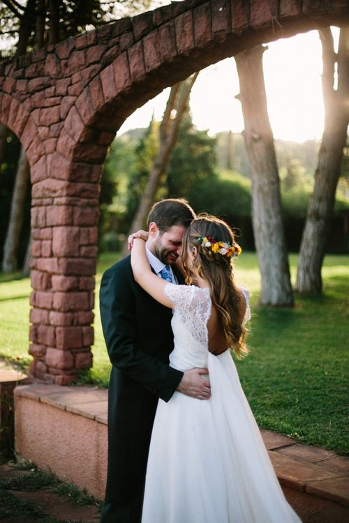Bride in Xavier González Wedding Dress & Bright Flower Crown with Groom in Traditional Morning Suit