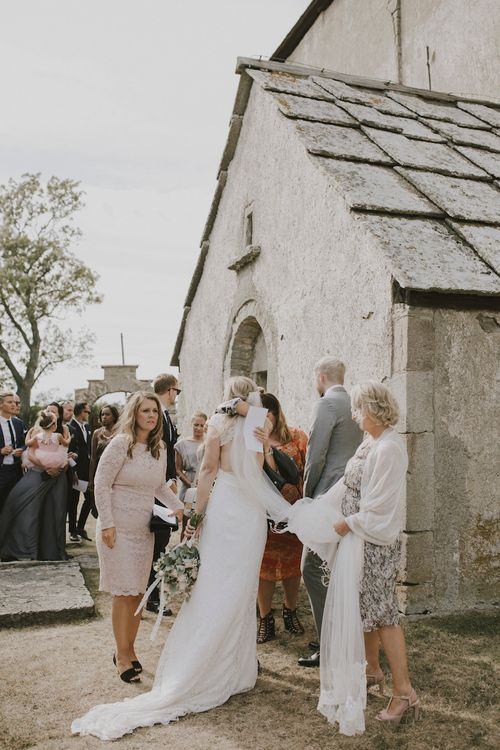 Bride hugging Wedding Guests outside the Church