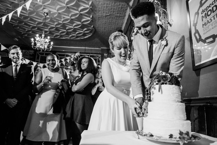 Cutting The Cake | Bride in Bespoke Tea Length Wedding Dress | Groom in Grey Jaeger Suit | 60s Inspired London Pub Wedding | The Peasant | Babb Photo