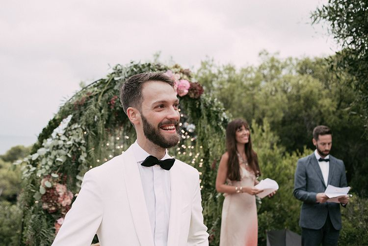 Wedding Ceremony   Groom at the Altar in Tailor Made Tom Black Suit   Stylish Outdoor Wedding at Masia Casa del Mar in Barcelona, Spain   Sara Lobla Photography   Made in Video Film