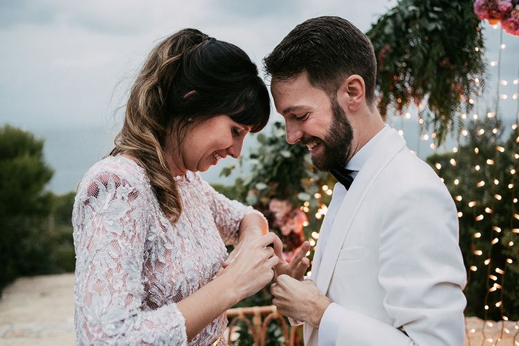 Exchanging of Rings   Bride in Embellished Ze García Bridal Gown with Front Split   Groom in Tailor Made Tom Black Suit   Stylish Outdoor Wedding at Masia Casa del Mar in Barcelona, Spain   Sara Lobla Photography   Made in Video Film
