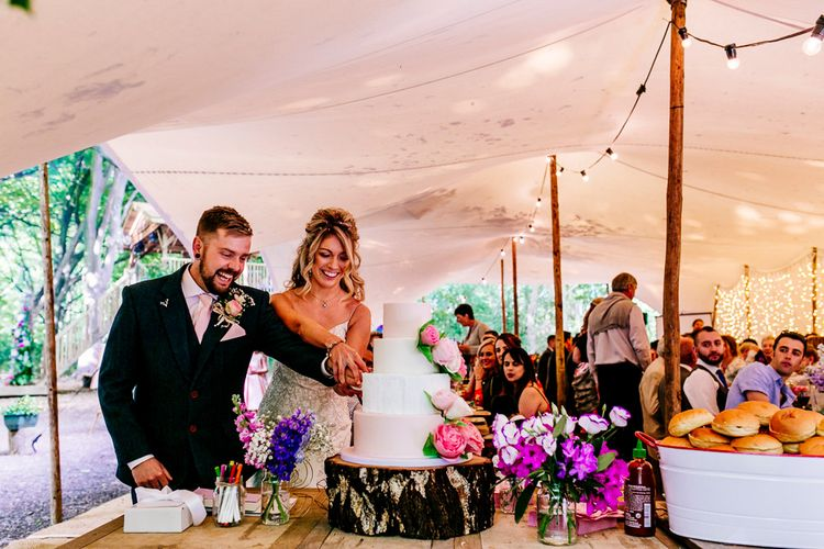 Cutting the Cake   Bride in Lace Anna Sorrano Gown   Groom in Tweed Vintage Suit Hire Suit   Epic Love Story Photography