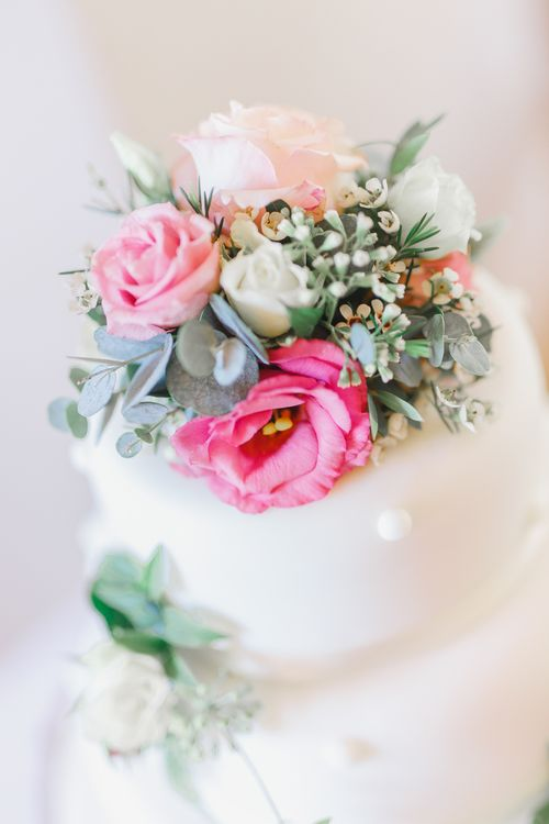 Traditional White Wedding Cake with Pink Flowers on a Tree Stump Cake Stand