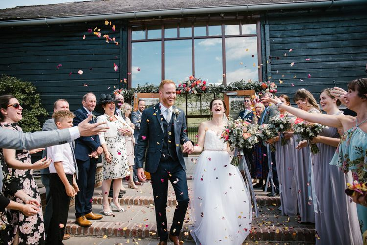 Confetti Exit | Bride in Sarah Seven Gown | Groom in Ted Baker & Next | DIY Wedding at Upwaltham Barns with Bright Flowers | Danielle Victoria Photography