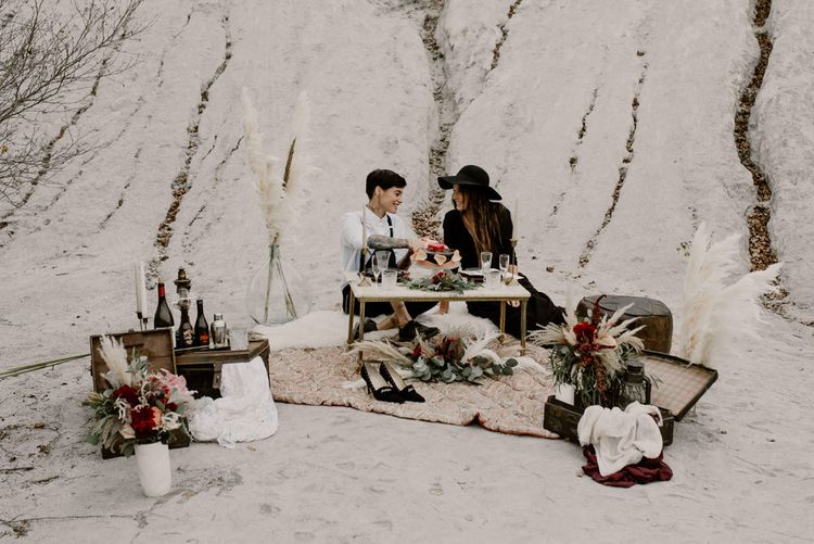 Sweetheart Table with Vintage Wedding Decor & Pampas Grass Floral Arrangements | Bride in Portez Vos Idées Black Wedding Dress | Pampas Grass, Eucalyptus & Red Rose Wedding Bouquet | Bride in Black Trousers, White Shirt & Braces | Wild Same Sex Couple Wedding Inspiration Shoot | Anne Letournel Photography