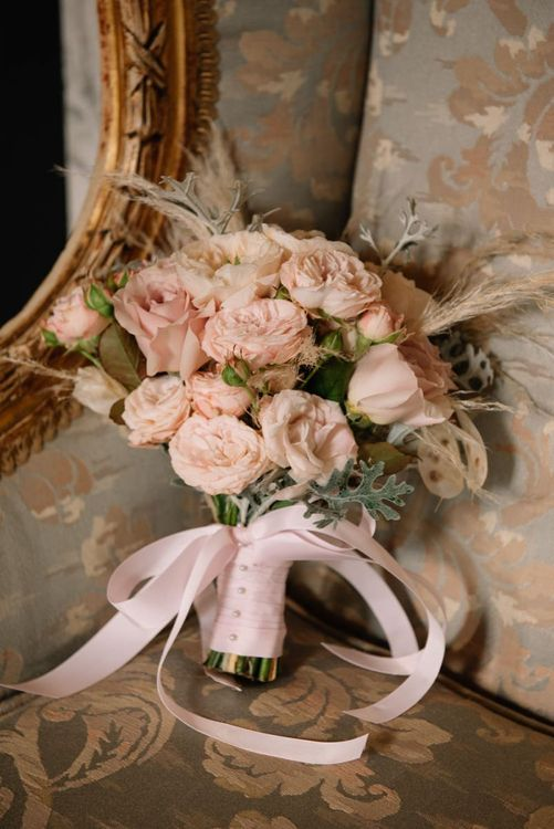 Romantic pink wedding bouquet tied with ribbon