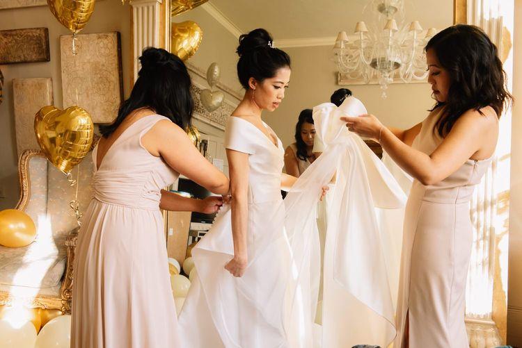 Bride on wedding morning putting on her wedding dress