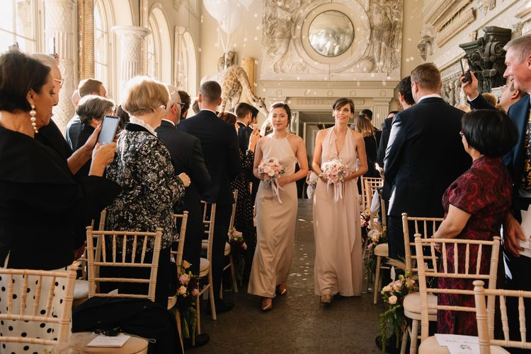 Bridesmaids in pink dresses walking down the aisle at Aynhoe Park