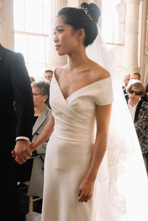 Classic bride in off the shoulder wedding dress and high bun