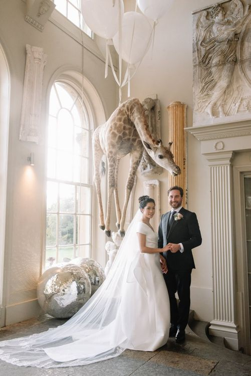 Bride and groom portrait standing in front of the infamous hanging giraffe at Aynhoe Park