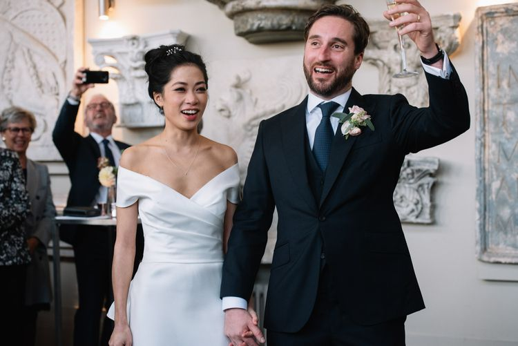 Bride and groom raising a glass during the wedding speeches