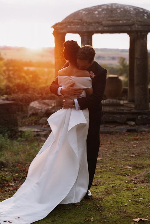 Groom embracing his bride during sunset