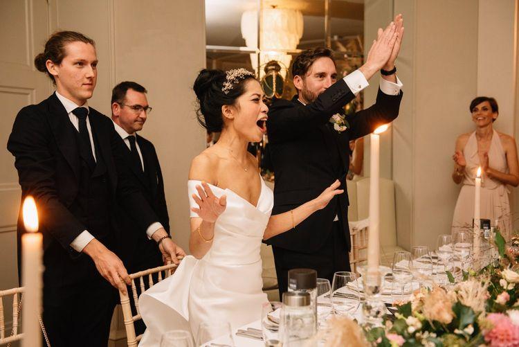 Bride and groom cheering during wedding breakfast