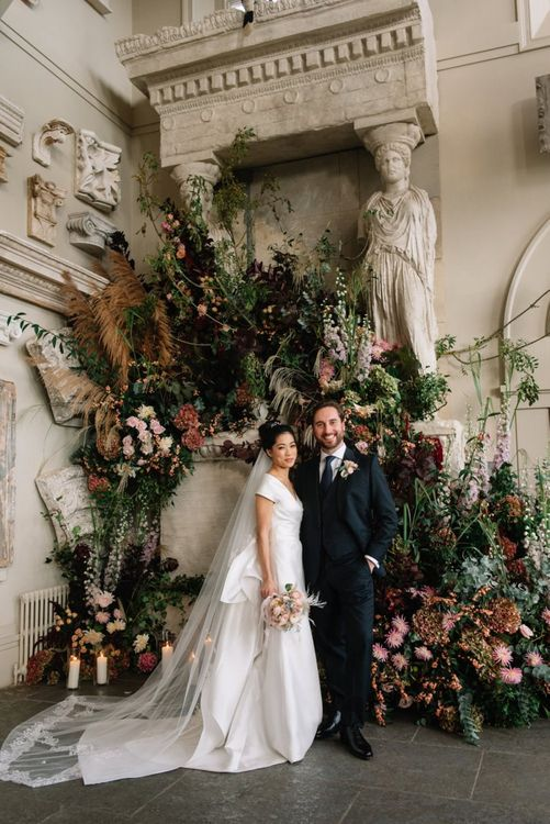 Deep red and green wedding flower back drop for bride and groom portrait