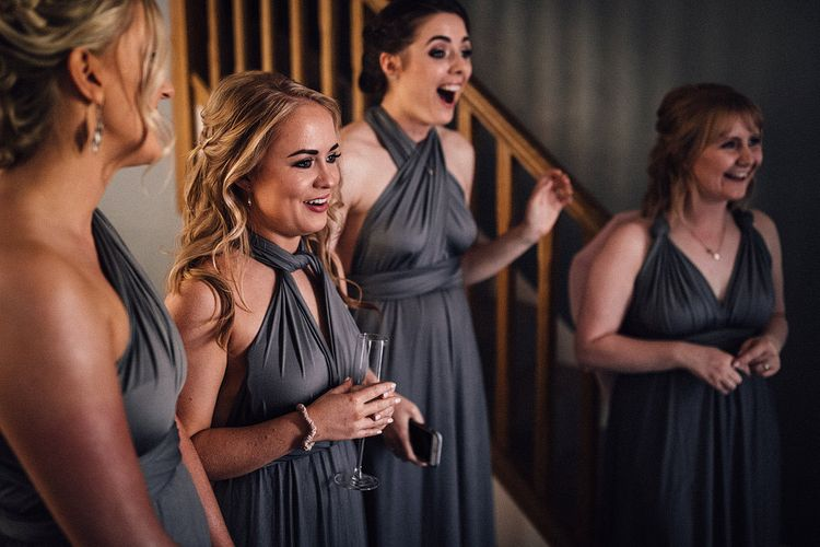 Bridesmaids in grey multiway dresses see the bride for the first time