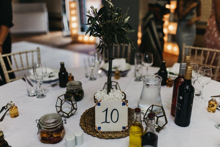 Table Styling | Mini Olive Tree in Terracotta Pot | Spanish Tile Table Number | Caramel Vodka Favours | Nottinghamshire Wedding with Spanish Vibes and Rewritten Bridesmaids Dresses | Kev Elkins Photography
