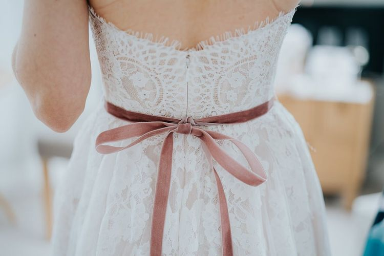 Back of brides delicate lace strapless  dress with ribbon detailing