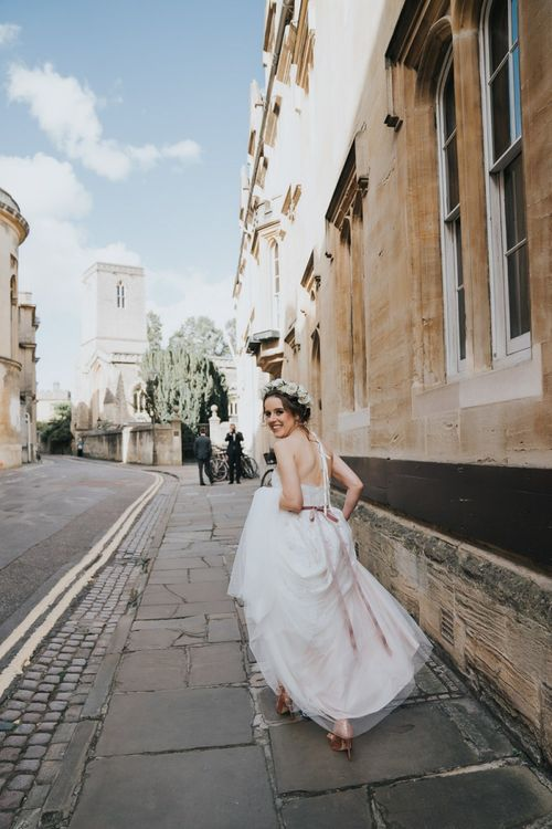 Bride walking through Oxford for her wedding wearing lace dress and flower crown