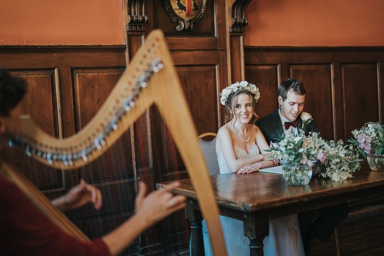 Bride and groom tie the knot at intimate civil ceremony with white bouquets and a harpist