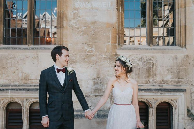 Bride and groom tie the knot at intimate Oxford wedding with a white floral bouquet and a flower head crown