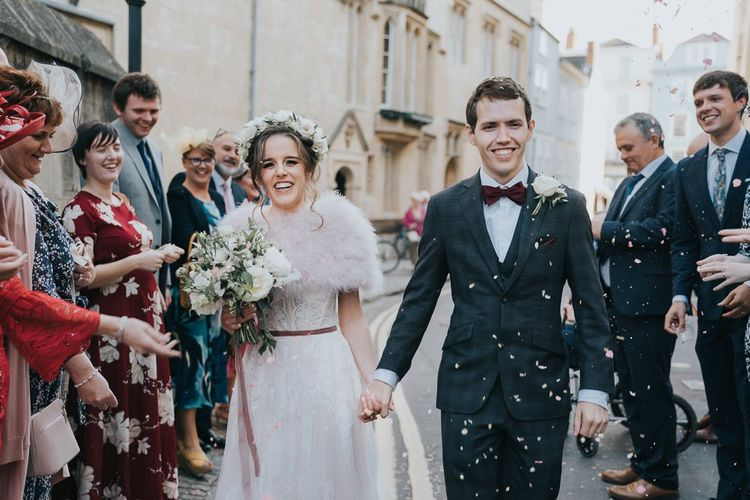 Bride and groom confetti shot at an intimate celebration with a bridal shrug and a flower head crown