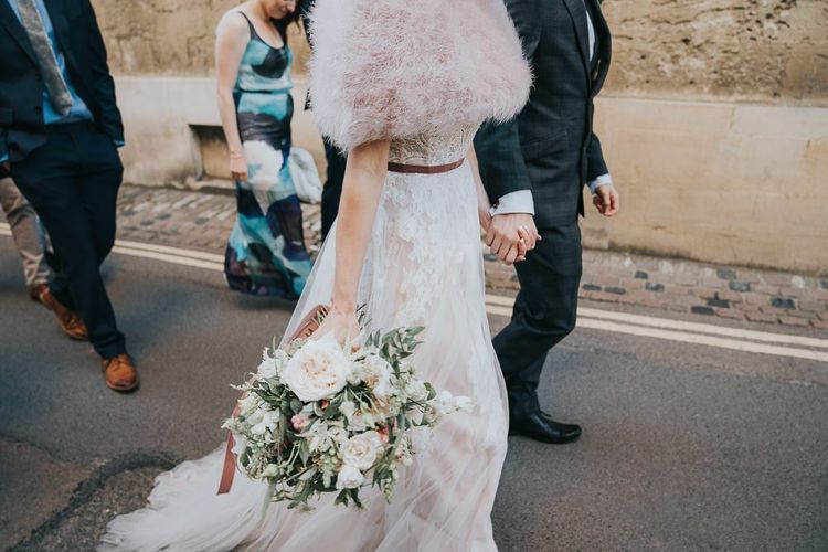 Bride and groom take a walk with their guests at an intimate celebration with a bridal shrug and a beautiful white floral bouquet