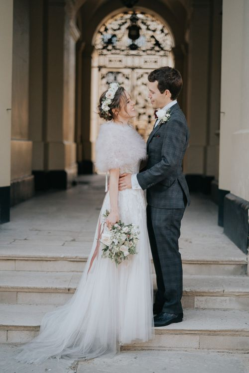Bride and groom enjoy an intimate celebration with a bridal shrug and a beautiful white floral bouquet