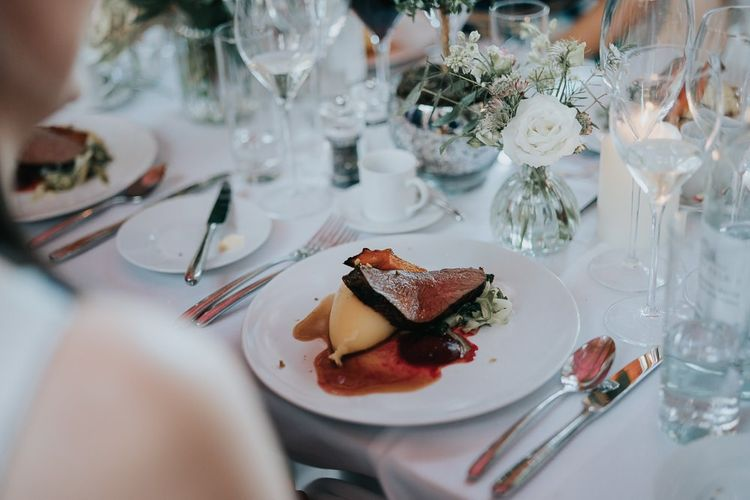 Food at the intimate and relaxed reception at Bodleian library with white floral centrepieces and candles