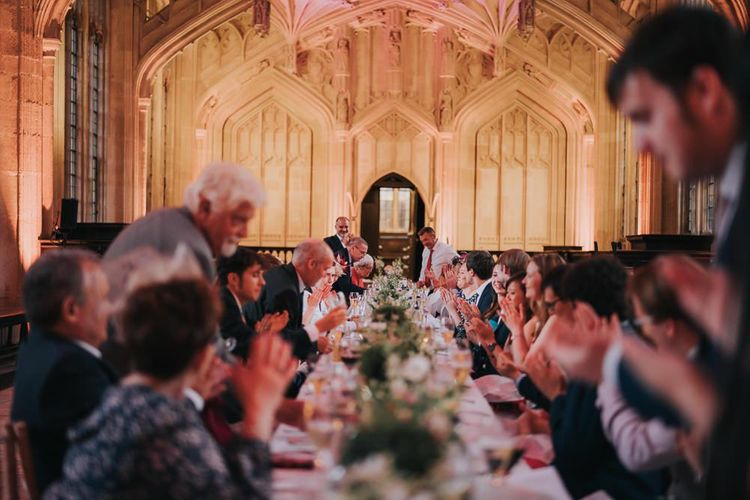 Guests enjoying an intimate and relaxed reception at Bodleian library with white floral centrepieces and stunning backdrop