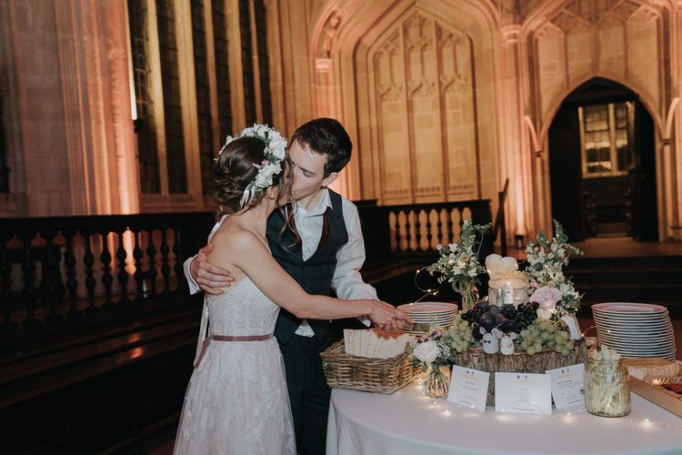 Bride and groom cutting the cheese tower cake at intimate celebration