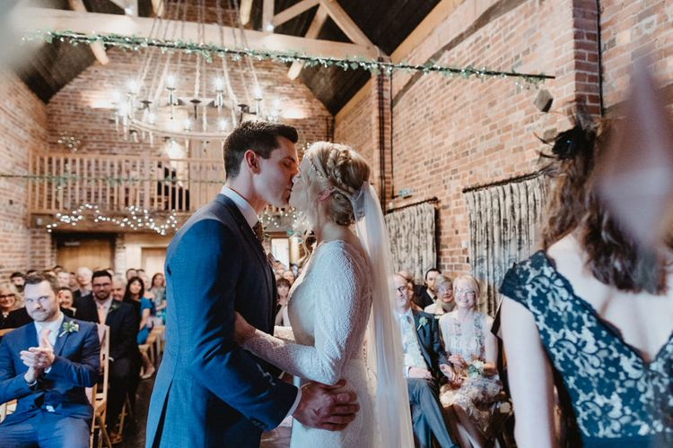 Bride in Lace Allure Bridals Wedding Dress and Groom in Navy Hugo Boss Suit Kissing at the Altar