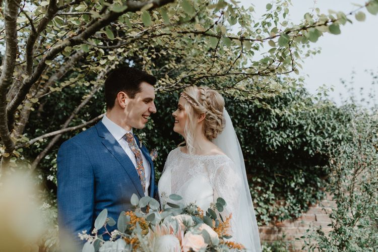 Bride in Lace Allure Bridals Wedding Dress with Long Sleeves and Groom in Blue Hugo Boss Suit Embracing