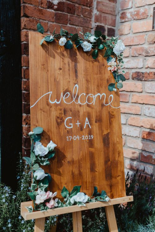 Wooden Welcome Sign with White Calligraphy Writing and Rose Floral Decor