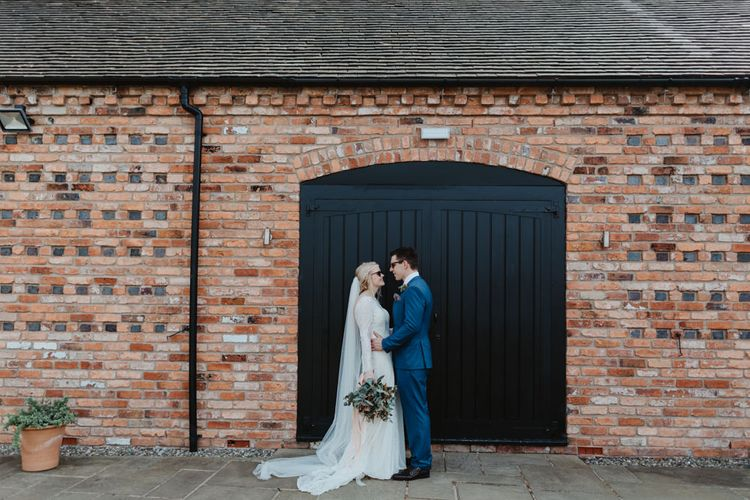 Bride in Lace Allure Bridals Wedding Dress with Long Sleeves and Groom in Blue Hugo Boss Suit