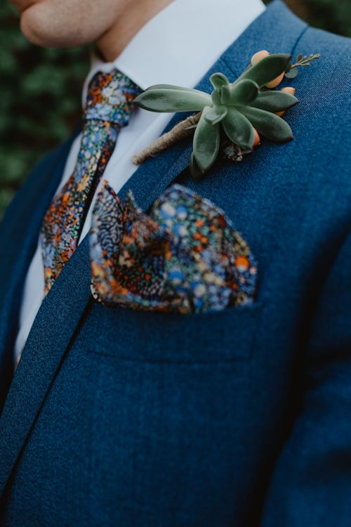 Groom in Blue Hugo Boss Suit with Succulent Buttonhole and Floral Tie and Pocket Square
