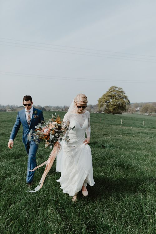 Bride in Lace Allure Bridals Wedding Dress with Long Sleeves and Groom in Blue Hugo Boss Suit Walking Through a Field